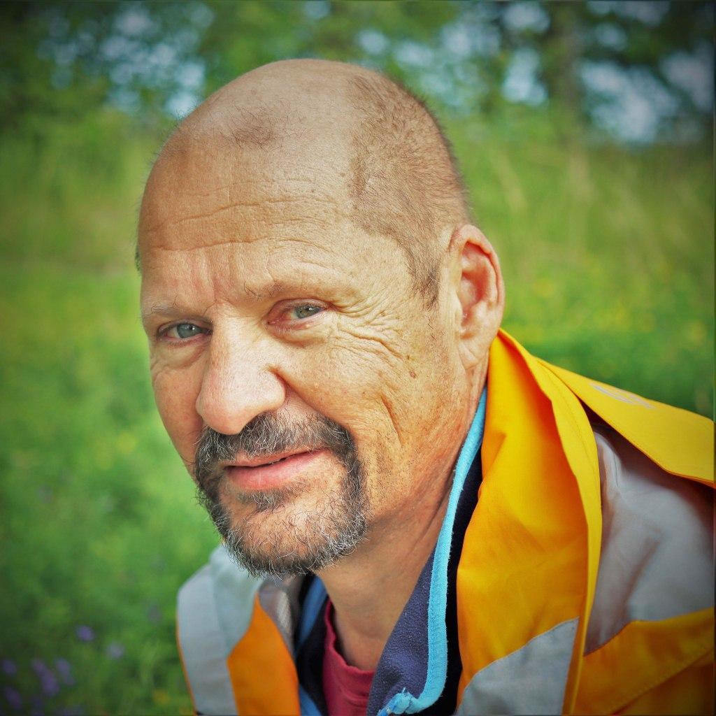 Jussi Mankki kasvokuva, ulkona retkeilyasussa, kamerahihna kaulassa